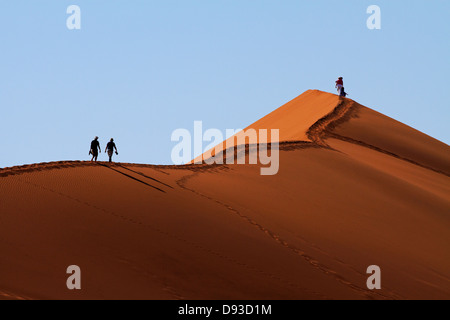 Tourists climbing sand dune beside Deadvlei, near Sossusvlei, Namib-Naukluft National Park, Namibia, Africa - Stock Photo
