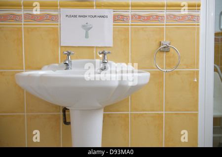 A sink in a bathroom with a  please wash your hands  sign   Stock. Wash Your Hands Sign In A Bathroom Showing Different Languages