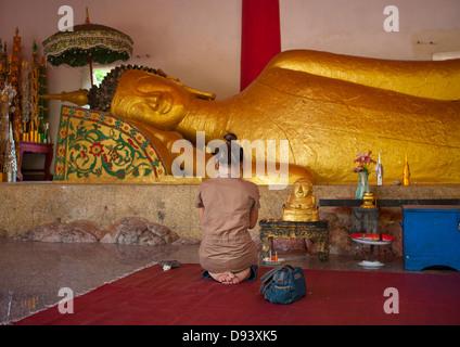 Man Praying In Front Of Lying Buddha In Pha Bat Monastery, Pakse, Laos - Stock Photo