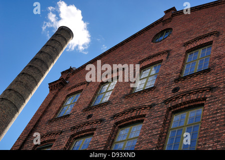 Factory building with smoke emitting from chimney, low angle view - Stock Photo