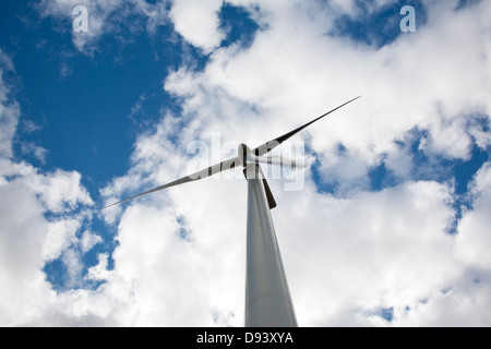 Wind turbine against cloudy sky, low angle view - Stock Photo