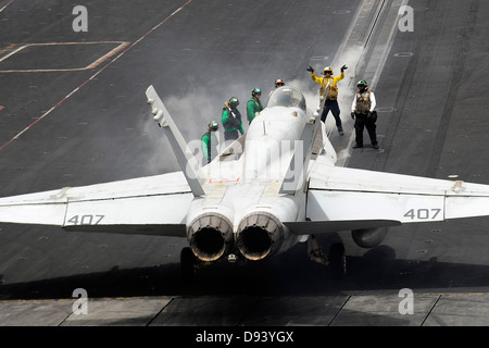 A Navy aircraft director guides an F/A-18C Hornet fighter aircraft onto a catapult on the flight deck of the aircraft - Stock Photo