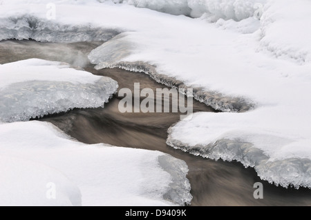 Water flowing through snow, close-up - Stock Photo