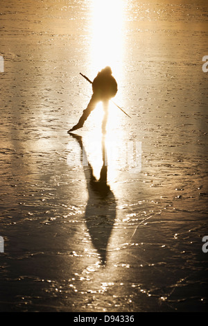 Person ice-skating on frozen lake - Stock Photo