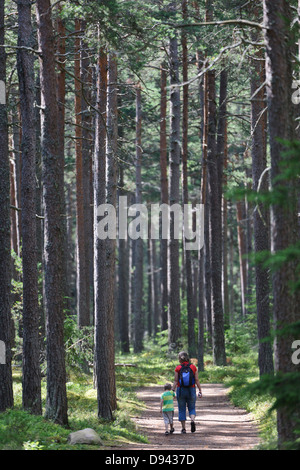 Mother and daughter walking together along forest trial - Stock Photo