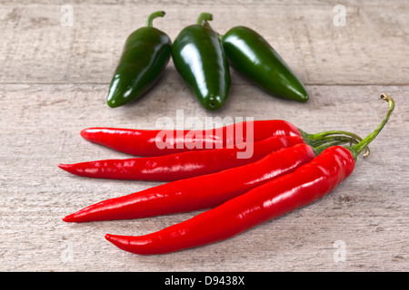 Red and Green Chilli Peppers on Weatherd Wood - red and green (jalapeno) chillis on a weathered wooden surface. - Stock Photo