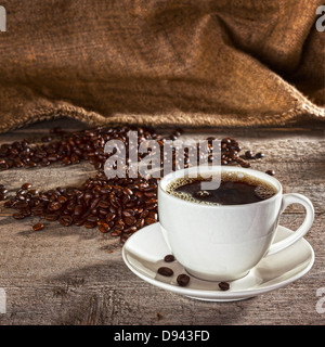 Coffee and Rustic Background - coffee cup and saucer filled with espresso, with coffee beans and burlap sack behind, - Stock Photo