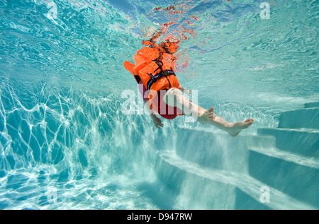 Child in life vest in swimming pool, low angle view - Stock Photo