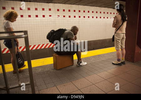 Waiting for a subway train, 34th Street station, NYC. - Stock Photo