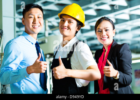 Shift supervisor or foreman, together with the owner or CEO and the Manager, standing proud in a factory - Stock Photo