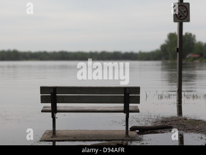 we see a park bench. The land is flooded and the bench is almost inaccessible; the sign post is also partially flooded - Stock Photo