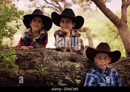 Three little boys dressed up like cowboys - Stock Photo