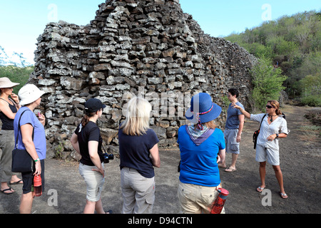 Tour guide explains the history of The Wall of Tears to tourists on Isabela Island in the Galapagos archipelago. - Stock Photo