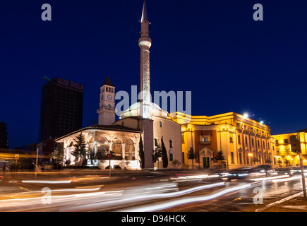 Ethem Bey Mosque surrounded by traffic motion trails at night. Skanderbeg square, Tirana, Albania - Stock Photo