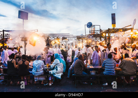 Djemaa el Fna square. People dining at the food stalls at dusk. Marrakesh, Morocco - Stock Photo