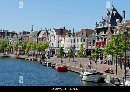 Shops, dwellings and boats line the quayside of the River Spaarne in the city of Haarlem in North Holland - Stock Photo