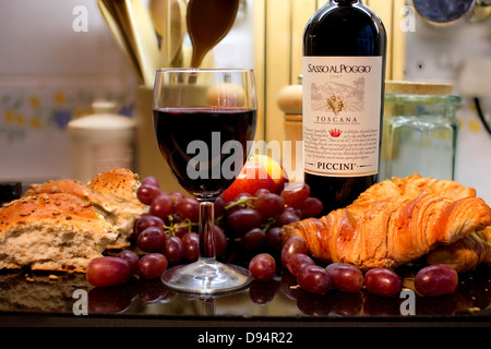 Food and drink image with glass of wine, bottle of wine,  red grapes, apple, bread and croissants on  a reflective - Stock Photo
