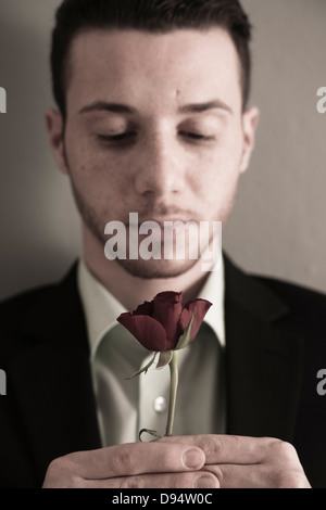 Close-up Portrait of Young Man holding Red Rose, Studio Shot - Stock Photo