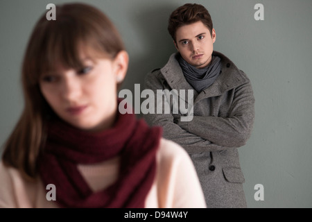 Portrait of Young Man Standing behind Young Woman, Looking at her Intensely, Studio Shot on Grey Background - Stock Photo