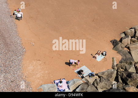 Sidmouth, Devon, England. June 10th 2013. Sidmouth beach and rocks with sunbathers enjoying leisure time. - Stock Photo
