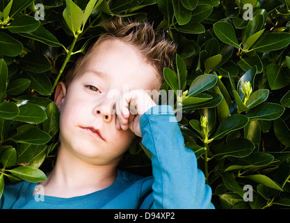Blond boy rubbing his eyes. The child is sleepy and tired. - Stock Photo