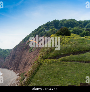 Sidmouth, Devon, England. June 10th 2013. Hang glider on the coast adjacent to the cliffs of the Jurassic coast. - Stock Photo