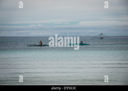 Two Filipinos paddling away in traditional outrigger boats on Dumaluan Beach on island of Bohol in Central Visayas, - Stock Photo