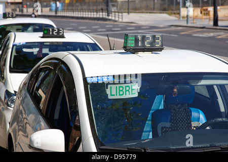 row of hybrid vehicle taxi cabs on a rank in valencia spain - Stock Photo