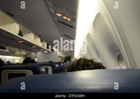 Curly hair detail of traveler in Delta airlines flight - Stock Photo