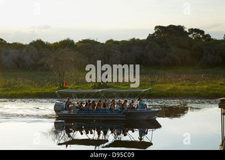 Tourist boat on Thamalakane River by Okavango River Lodge, Maun, Okavango Delta, Botswana, Africa - Stock Photo