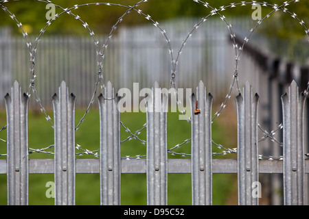 Spiked metal railings and razor wire around a secure compound. - Stock Photo