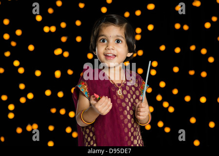 Girl holding fire crackers and smiling in front of Diwali decoration - Stock Photo