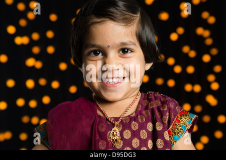 Portrait of a girl smiling in front of Diwali decoration - Stock Photo