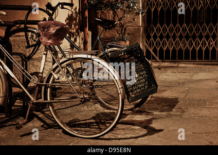 vintage bicycles parked on a street at night alone and - Stock Photo
