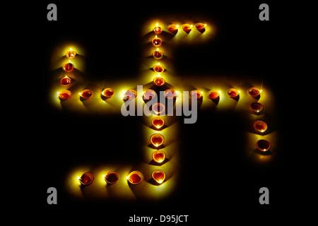 Burning oil lamps in swastika shape at Diwali festival - Stock Photo