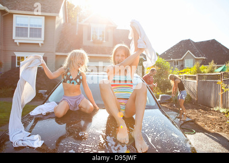 A family washes their car in the driveway of their home on a sunny summer afternoon in Portland, Oregon, USA