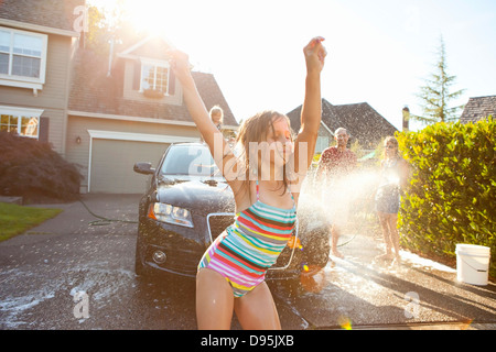Young girl dances while family washes car in the driveway of their home on a sunny summer afternoon in Portland, - Stock Photo