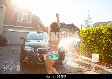 Young girl dances while family washes their car in driveway their home on sunny summer afternoon in Portland Oregon - Stock Photo