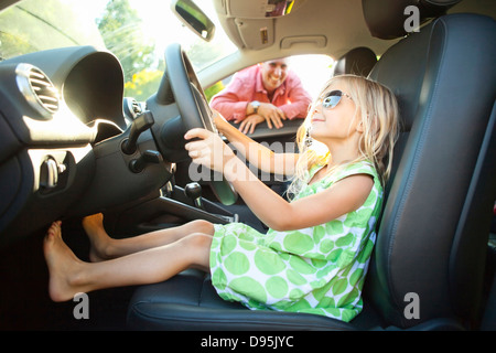 Little girl sitting in Driver's seat car pretending be old enough drive as her smiling father watches on on sunny - Stock Photo