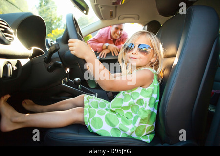 Portrait little girl sitting in driver's seat car pretending be old enough drive as her smiling father watches on - Stock Photo