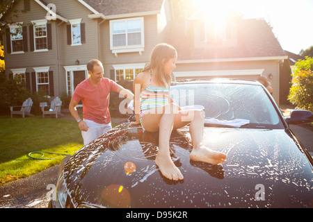 Family washing their car in the driveway of their home on a sunny summer afternoon in Portland, Oregon, USA