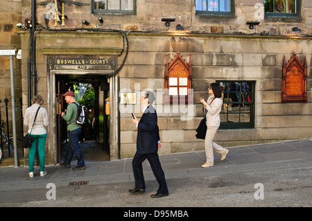 Tourists passing the entrance to Boswell's Court and The Witchery Restaurant on Edinburgh's Royal Mile. - Stock Photo