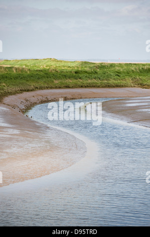 A river leading out to the river Humber estuary seen at low tide. North Lincolnshire England UK - Stock Photo