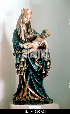 Virgin Mary Holding Baby Jesus Statue And Flowers Stock