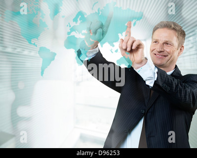 Businessman giving presentation in office, smiling - Stock Photo