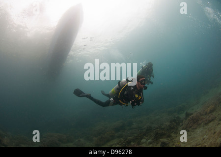 Divers descend from boat in plankton-rich water in the Lembeh Straits, Indonesia - Stock Photo