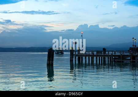Peaceful evening on Lago di Garda in Italy, with Jetty pier in Sirmione and the last ferry boat for the day. - Stock Photo