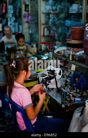 Family workshop with adults on sewing machines and young girl cutting fabric in Bangkok, Thailand - Stock Photo