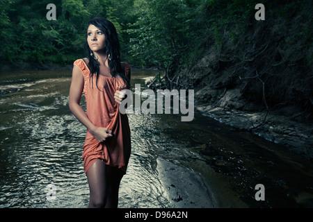 Woman in wet dress standing in creek - Stock Photo