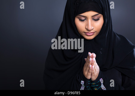 religious young Muslim woman praying over black background - Stock Photo